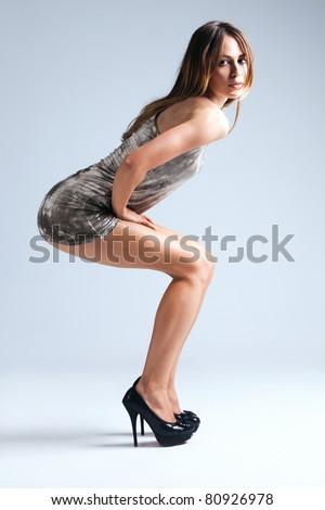 young woman in short dress and high heels, studio shot, full body shot - stock photo