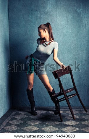 young woman in shorts and boots in old grunge room, full body shot