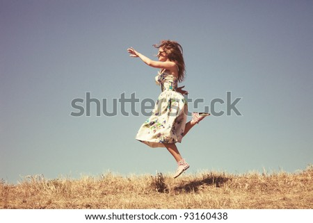 young woman in silk dress on top of the hill jumps, sky in background, retro colours, grain added - stock photo