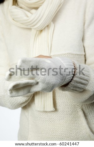 Young woman in soft white sweater, wearing mittens