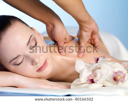 Young woman in spa salon having massage of  shoulder - horizontal - stock photo