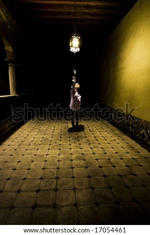 Young woman in spooky corridor - stock photo