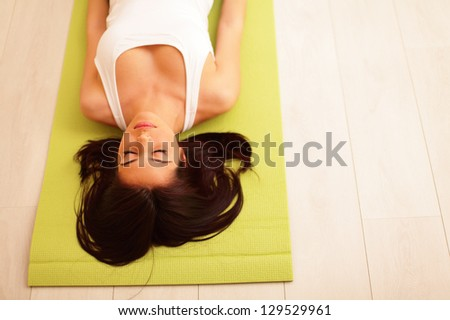 Young woman in sport cloths lying on the yoga mat - stock photo