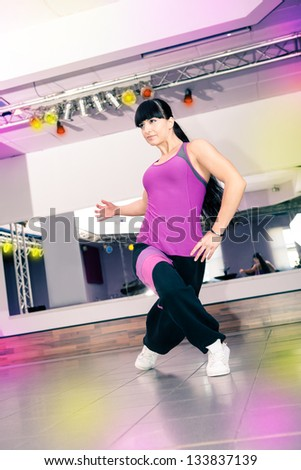 young woman in sport dress at an aerobic and zumba exercise