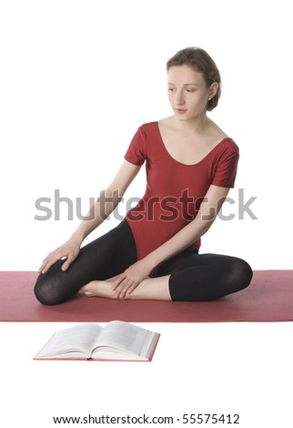 Young woman in sports clothes reading a book - stock photo