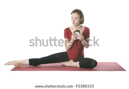 Young woman in sports clothes trying to hide a chocolate bar - stock photo