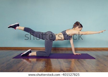 Young woman in sportswear doing sport at home - stock photo