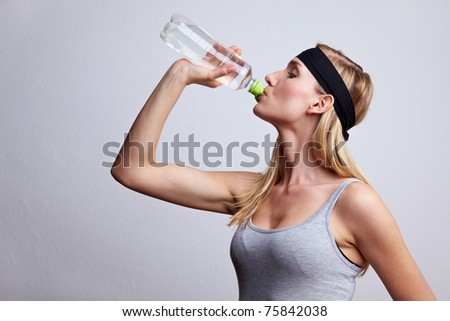 Young woman in sportswear drinking water from a plastic bottle - stock photo