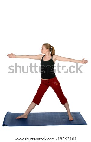 young woman in standing yoga pose on a blue mat - stock photo