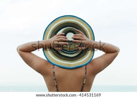 Young woman in straw hat standing by the sea and looking to horizon - stock photo