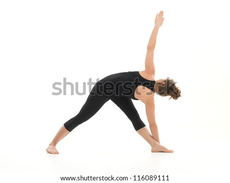 young woman in stretching yoga posture, dressed in black on white background - stock photo
