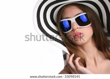 young woman in striped hat and sunglasses on background blue sky - stock photo
