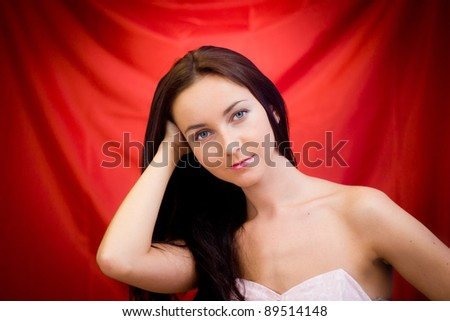 Young woman in studio against red background - stock photo