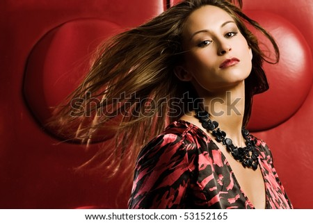 Young woman in studio with windblown hair in red dress - stock photo