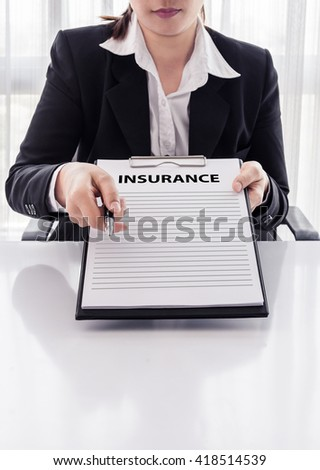 young woman in suit in his office showing an insurance policy and pointing with a pen where the policyholder must to sign