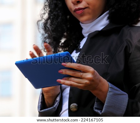 Young woman in suit using a tablet outdoor (half photo)