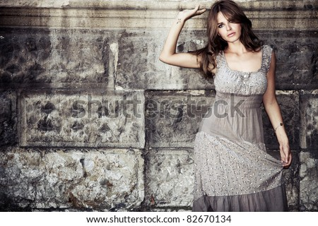 young woman in summer dress  against old stone wall, outdoor shot - stock photo