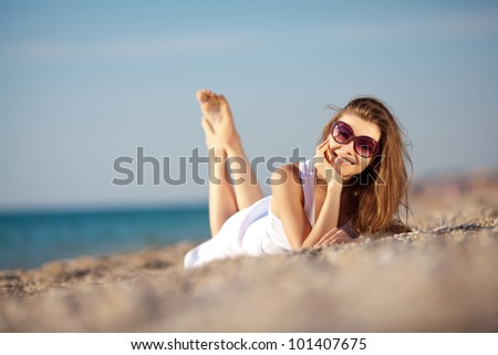 Young woman in summer dress in sunglasses lieing on sand near the sea - stock photo