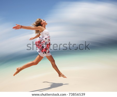 Young woman in summer dress jumping on sand. Motion blurred background - stock photo