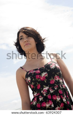 Young woman in summer dress on beach, with the wind blowing through her hair. - stock photo