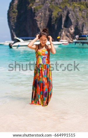Young woman in summer dress relaxing on the beach.