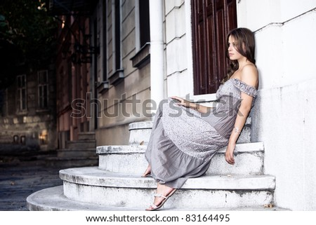 young woman in summer dress sit on stairs, waiting for someone, outdoor shot - stock photo