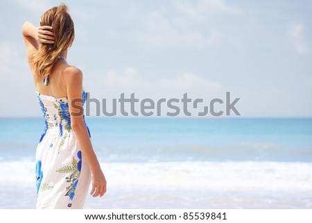 Young woman in summer dress standing on a beach and looking to the horizon - stock photo