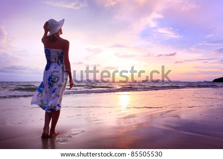 Young woman in summer dress standing on a sandy beach - stock photo