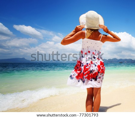 Young woman in summer dress standing on sand and holding straw hat - stock photo