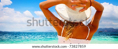 Young woman in summer dress standing on sand and holding straw hat looking to a sky - stock photo