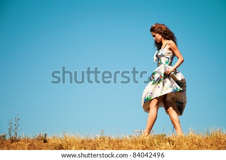 young woman in summer dress walk through the grass, blue sky in background, summer day - stock photo