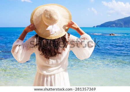 Young woman in summer dress with  straw hat looking to a sky and sea - stock photo