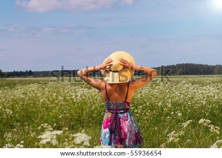 Young woman in summer hat enjoying nature - stock photo