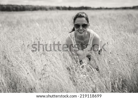 Young woman in summer walking on a meadow. A girl stands in the middle of a field on a sunny day. Field, flowers beauty, nature,  - The concept of country vacation.  - stock photo