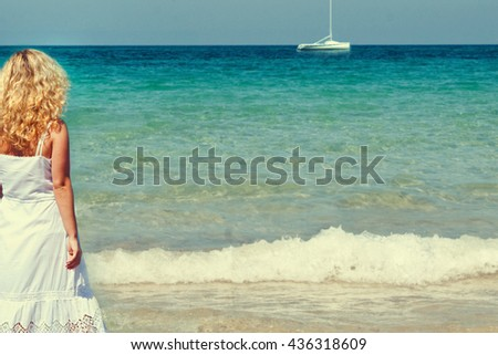 Young woman in summer white dress standing on beach and looking to the sea. - stock photo