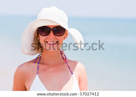 Young woman in sun glasses and white hat on a beach. Sunny vacation on sea - stock photo