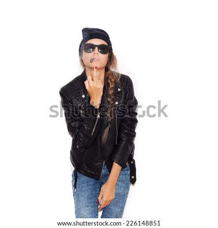 Young woman in sunglasses and black beanie smoking and showing middle finger over white background, not isolated - stock photo