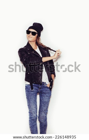 Young woman in sunglasses and black leather jacket and beanie pulling her scythe.  White background, toned, not isolated - stock photo