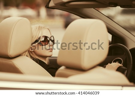 Young woman in sunglasses driving convertible car. Female blond fashion model outdoor - stock photo