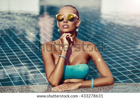 Young woman in sunglasses in the pool - stock photo
