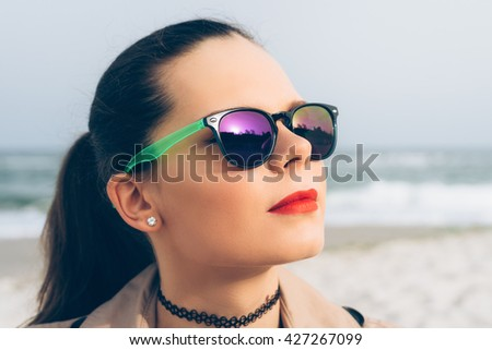 Young woman in sunglasses looks at the sun on the beach in spring - stock photo