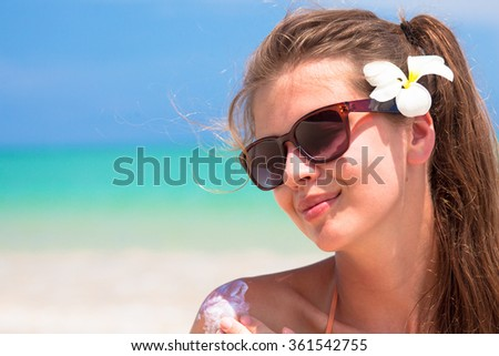 Young woman in sunglasses putting sun cream on shoulder - stock photo