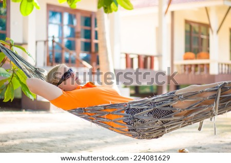 Young woman in sunglasses relax in hammock under palm trees on tropical beach - stock photo