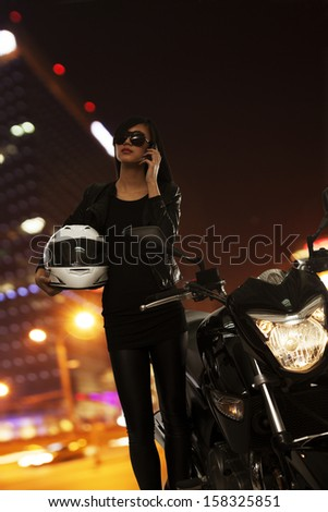 Young woman in sunglasses talking on the phone and standing next to her motorcycle