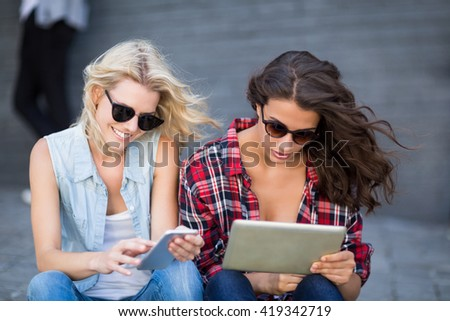 Young woman in sunglasses using digital tablet - stock photo