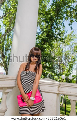 Young woman in sunglasses with pink handbag, a lot of copy space. - stock photo