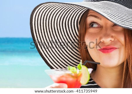 young woman in sunhat drinks cocktial