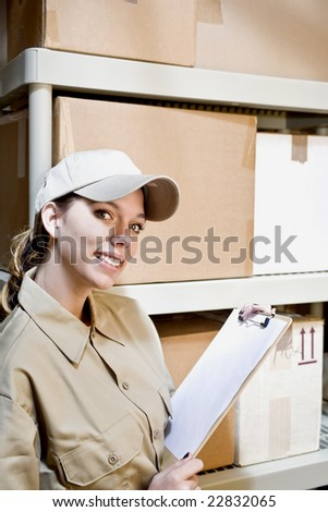Young woman in supply room taking inventory - stock photo