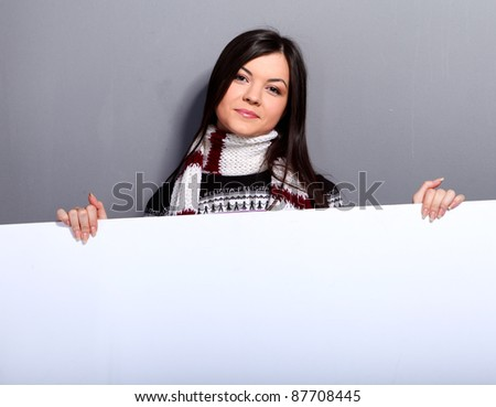 Young woman in sweater and scarf with empty placard - stock photo