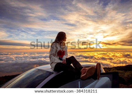 Young woman in sweater with heart shape enjoying beautiful cloudscape sitting on the car roof above the clouds on the sunrise - stock photo